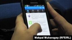 Cмартфон арқылы интернет қарап отырған адам. Астана, 23 желтоқсан 2012 жыл. (Көрнекі сурет)