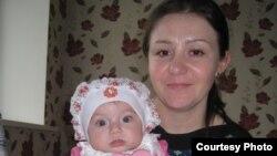 Виктория Ким мемлекеттік қордан уақытша берілген пәтерінде қызымен отыр. Қарағанды, 18 қыркүйек 2013 жыл.
