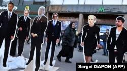 A woman walks past cutouts depicting presidential candidates Yuriy Boyko (left), Yulia Tymoshenko (2nd right), Volodymyr Zelenskiy (right), as well as Russian President Vladimir Putin (2nd left), oligarch Ihor Kolomoyskiy (3rd left) and politician Serhiy Taruta in Kyiv on March 28.