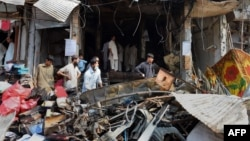 Pakistani merchants gather beside their damaged shops in Peshawar on September 30, the day after a bomb blast.