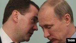 Президент России Дмитрий Медведев (слева) и премьер-министр России Владимир Путин шепчутся на заседании правительства. Москва, 27 декабря 2011 года.