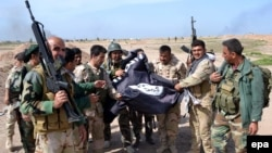 Iraqi Kurdish Peshmerga soldiers hold a flag belonging to the Islamic State militant group after they regained control of an area west of Kirkuk in March 2015.