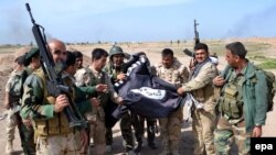 Kurdish Peshmerga soldiers pose with a flag belonging to Islamic State after they regained control of an area west of Kirkuk in Iraq from the Islamist extremists earlier this year.