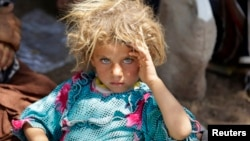 A Yazidi girl fleeing violence in the Iraqi town of Sinjar rests at the Iraqi-Syrian border crossing in mid-August.