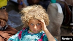 Девочка из семьи езидов во временном лагере беженцев