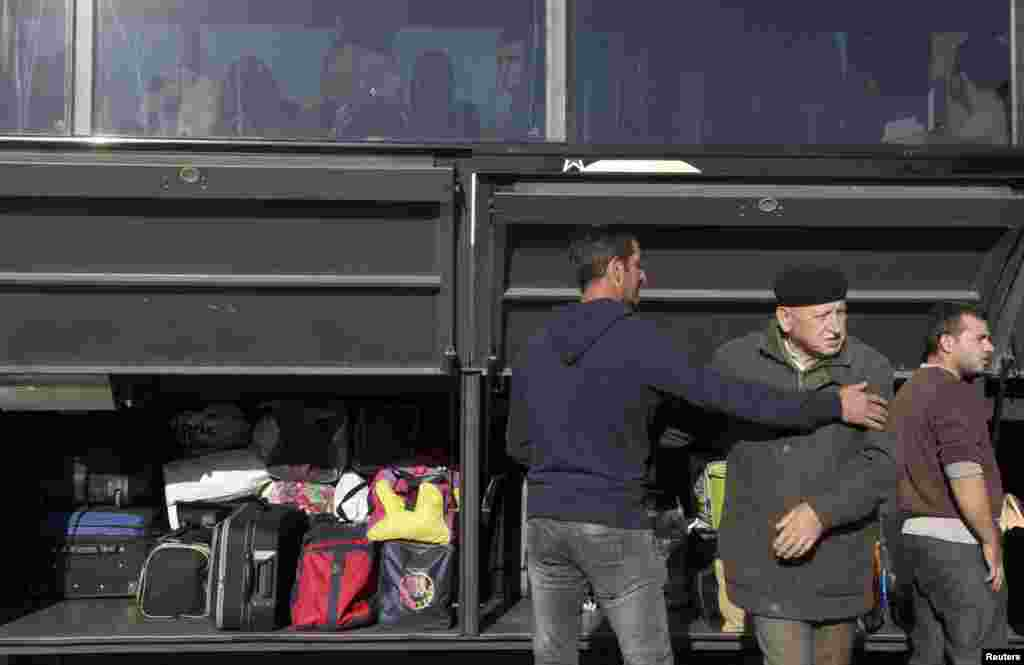 Passengers load their baggage into a bus.
