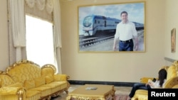 A woman relaxes underneath a photo of President Gurbanguly Berdymukhammedov at the resort of Avaza.