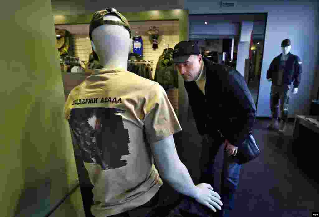 "A man looks at a mannequin dressed in a T-shirt with an aerial view of Russian air strikes in Syria and bearing the words in Russian ""Support Assad"" at a Russian Army store in downtown Moscow. (epa/Yury Kochetkov)"