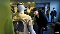 "A man looks at a mannequin dressed in a T-shirt with an aerial view of Russian air strikes in Syria and bearing the words ""Support Assad"" at a Russian Army store in Moscow."