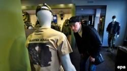 """Majica sa natpisom """"Podrži Asada"""" i fotografijom ruskih audara u Siriji u jednom od izloga trgovine oružja u Moskvi, oktobar 2015."""