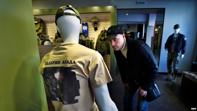 """A man looks at a mannequin dressed in a T-shirt with an aerial view of Russian air strikes in Syria and bearing the words """"Support Assad"""" at a Russian Army store in Moscow."""