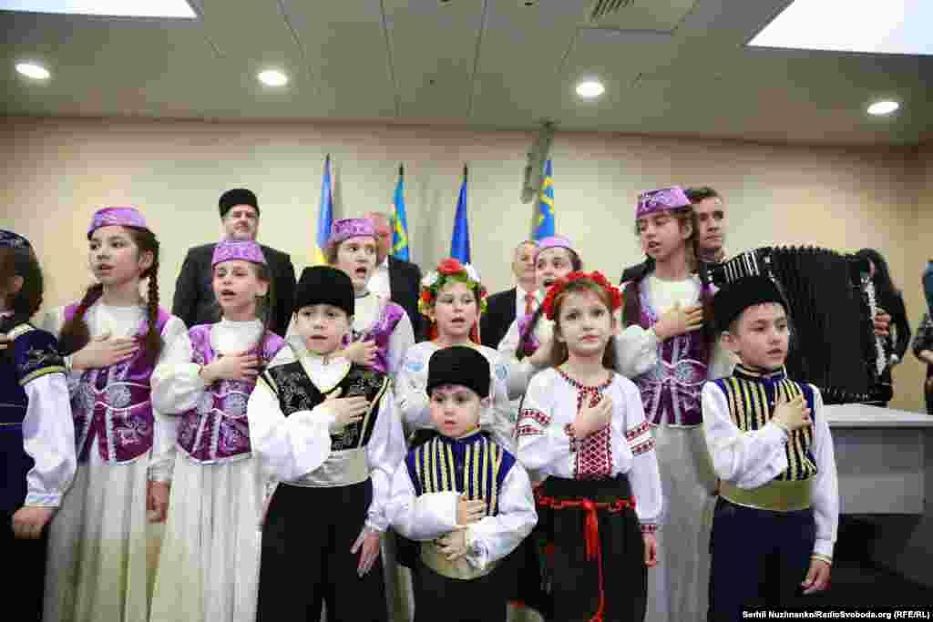 На церемонії вітання звільнених Ільмі Умерова і Ахтема Чийгоза дитячий хор виконав український і кримськотатарський гімни.