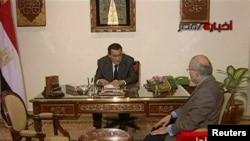 Хосни Мубарак (слева) беседует с премьер-министром Ахмедом Шафиком, 29 января 2011