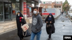 Residents of Qom wear face masks after Iranian authorities reported the deaths of two men in the city.