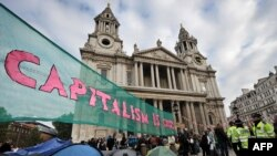 Demonstrators protest against austerity measures and corporate greed in front of St. Paul's Cathedral in London.
