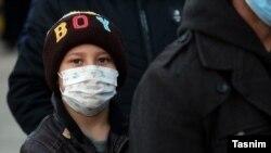 Хлопчик чекає на медичний огляд в Кумі, епіцентрі спалаху коронавірусу в Ірані, 27 лютого 2020 року
