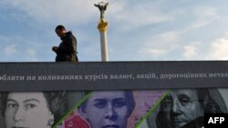 A man stands next to a billboard in Kyiv showing the British , U.S., and Ukrainian banknotes.