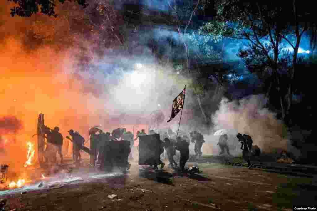 18 қарашада полицейлер PolyU университетін босатпақ болды. Полиция кампусты қоршап, наразыларға көзден жас ағызатын газ, суатқыш қолданды. Фотоны сол маңда болған қазақстандық студент түсірген.