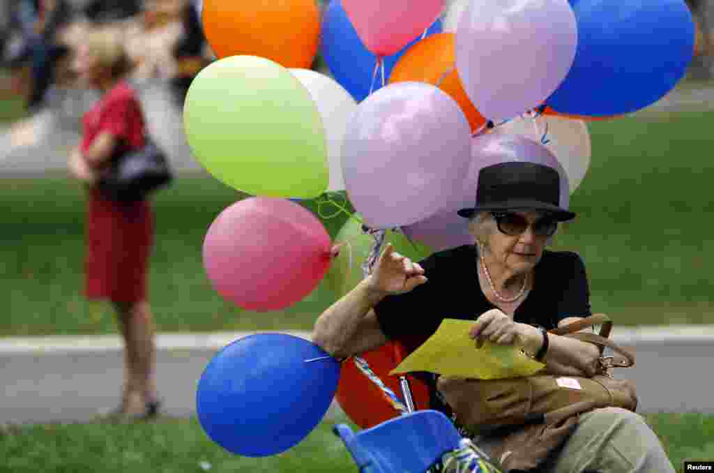 An activist sits on a bench holding onto multicolored balloons to mark International Day Against Homophobia and Transphobia in Belgrade. (AFP/Saul Loeb)