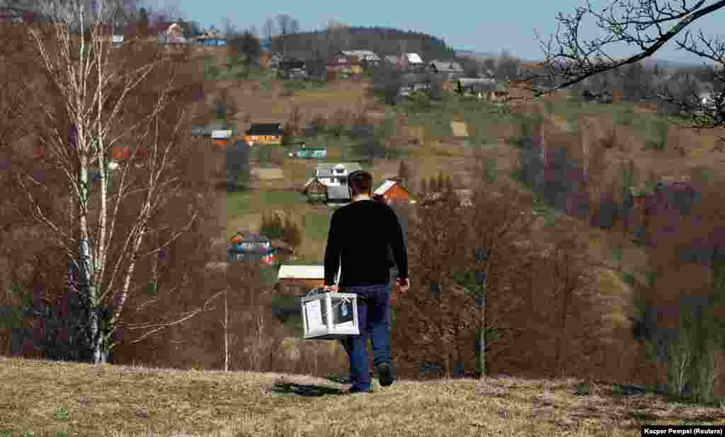 A member of a local election commission carries a mobile ballot box during voting in the village of Kosmach, western Ukraine. (Reuters/Kacper Pempel)