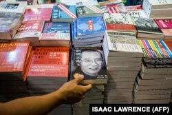 یک بازدیدکننده در نمایشگاه کتاب هنگکنگ در اواخر تیرماه ۹۶، نسخهای از زندگینامه شیائوبو لیو، برنده چینی نوبل ادبیات را به دست گرفته است.
