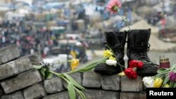 Военные ботини и цветы на баррикадах в центре Киева. 25 февраля 2014 года.