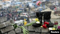 Military boots and flowers are seen at a makeshift memorial for those killed in recent violence in Kyiv on February 25.