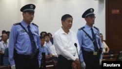 Bo Xilai gjatë procesit gjyqësor kundër tij i ruajtur nga dy policë