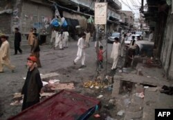 This photograph taken on July 26, 2013 show residents gathering at the site of twin bomb explosions in Parachinar