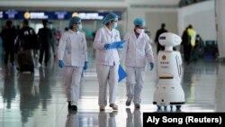 Китайские врачи рядом с роботом-полицейским. Апрель 2020 года.