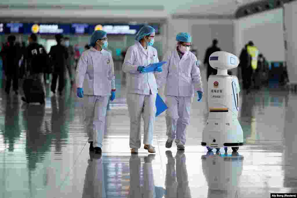 Medical workers walk by a police robot at the Wuhan Tianhe International Airport after travel restrictions to leave Wuhan, the capital of Hubei province and China's epicentre of the novel coronavirus disease (COVID-19) outbreak, were lifted, April 8, 2020.