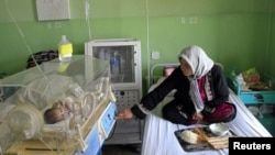 A woman helps look after her newborn baby at Cure International's hospital in Kabul, Afghanistan.