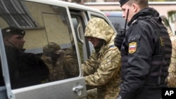 A Ukrainian sailor (left) is escorted by a Russian police officer from a court in Simferopol, Crimea, on November 28.