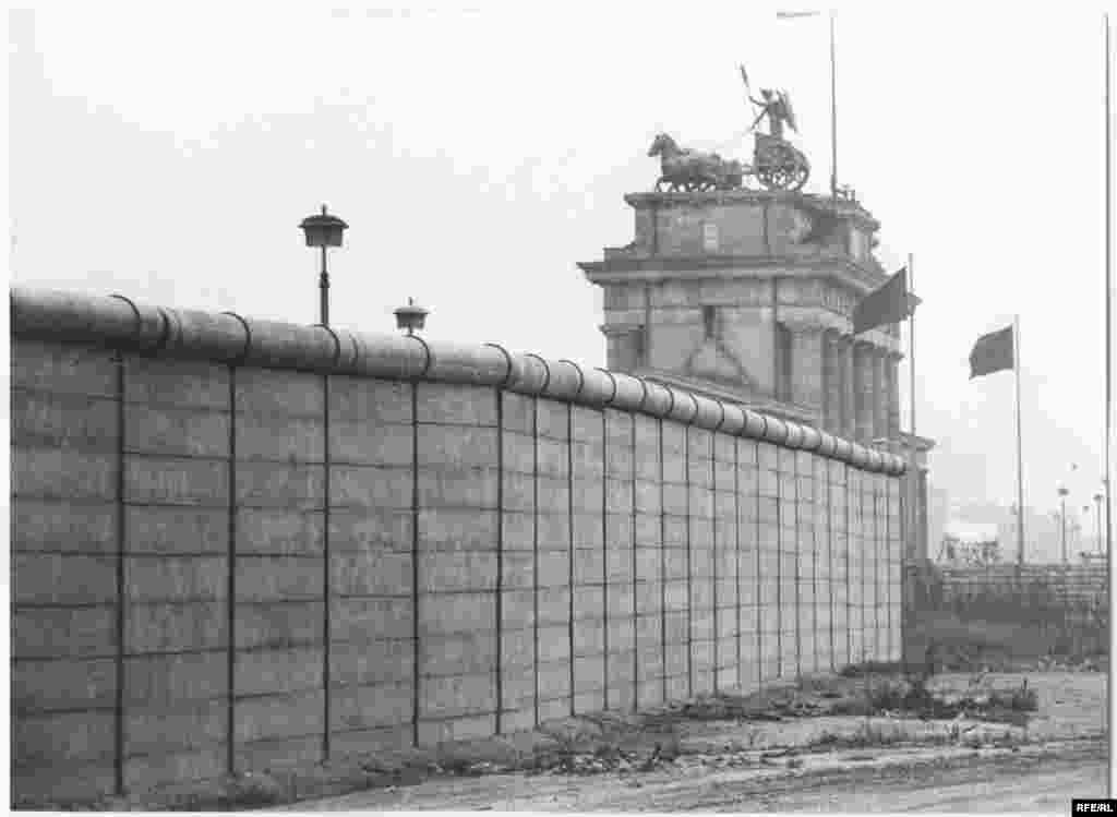 """The wall with the Brandenburg Gate in the background.On June 12, 1987, near this site, U.S. President Ronald Reagan famously demanded of Soviet leader Mikhail Gorbachev: """"Mr. Gorbachev, tear down this wall."""""""