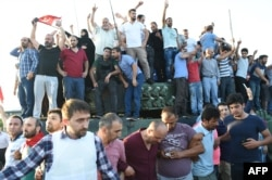 People rally on a tank after they took over a military position on the Bosphorus bridge.
