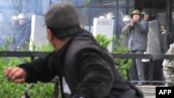 """""""Апрель толқуы"""" кезінде шерушіге қару кезеніп тұрған қырғыз полицейі. Бішкек, 7 сәуір 2010 жыл"""