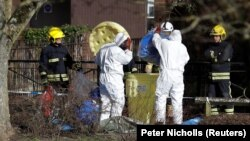 Officials in protective suits near the park bench where Sergei Skripal and his daughter Yulia were found poisoned