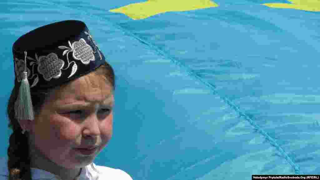 Дівчинка несла велике полотнище кримськотатарського національного прапору
