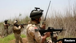 Iraqi security forces patrol outside the city of Fallujah.
