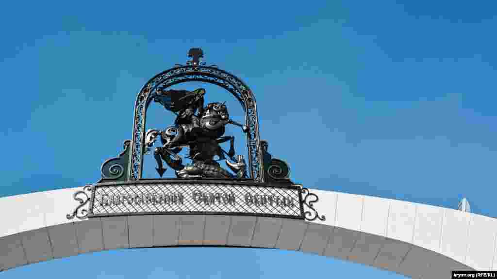 Арку на входе венчает фигура святого Георгия Победоносца, поражающего копьем змея