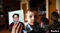 Artur, son of Svetlana Davydova, holds up a photo of his mother to the camera, at their home in Vyazma