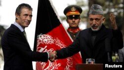 Afghan President Hamid Karzai (right) welcomed NATO Secretary-General Anders Fogh Rasmussen to Kabul on October 18.