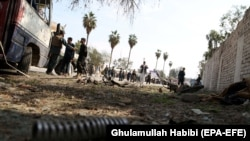 Afghan policemen inspect the scene after a deadly blast in Jalalabad on March 19.