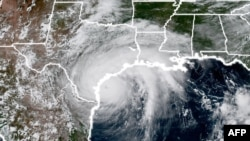 This National Oceanic and Atmospheric Administration satellite image taken on August 25, 2017, shows Hurricane Harvey (L) approaching the coast of Texas.