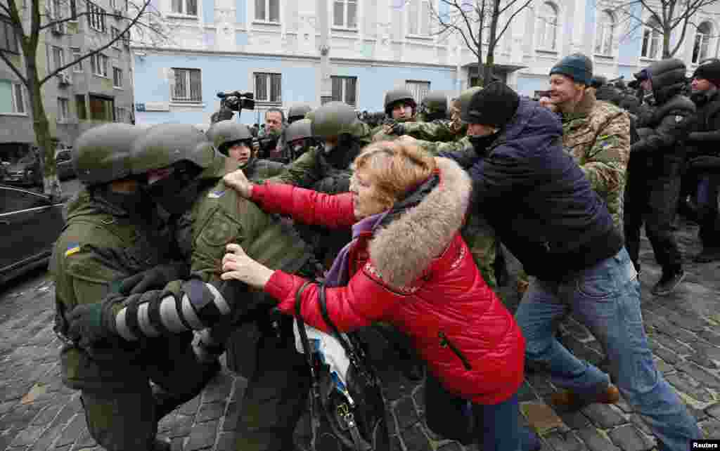 Saakashvili supporters clash with National Guard officers in Kyiv. The numbers of protesters swelled quickly after an associate of Saakashvili published the address of the apartment the police stormed.