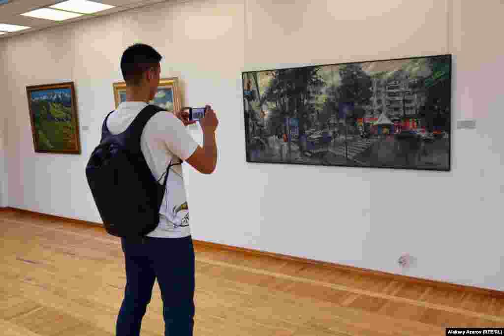 Сразу после двух картин с видами Нур-Султана находится алматинский городской пейзаж «После дождя» Сергея Уткина. Этот молодой человек из группы китайских туристов выделил именно ее, а не соседствующие картины, чтобы запечатлеть на память.