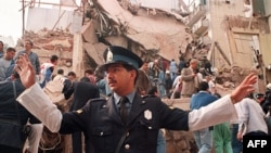 A policeman prevents people from approaching the site where a powerful explosion destroyed a seven story building housing, the Jewish Mutual Association of Argentina, in Buenos Aires, 18Jul1994