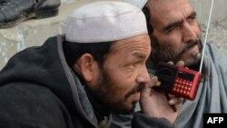 دو تن در حال گوش دادن به رادیو در یکی از روستاهای ننگرهار