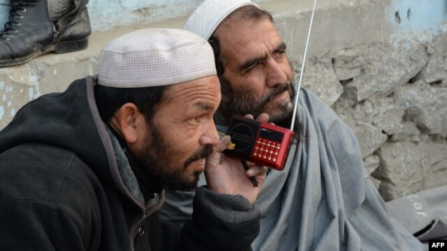 Afghan men listen to a radio broadcast by the Voice of the Caliphate station run by Islamic State in December 2015.
