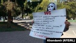 O'zbekistonlik boshpana izlovchi Karimjon Bishkekdagi BMT uyi oldida flesh-mob o'tkazmoqda.